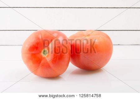 Two ripe tomatoes against a light background propped up