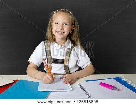 beautiful happy blond junior schoolgirl smiling while doing school homework writing on notepad with pen having fun in children education concept and academic success concept