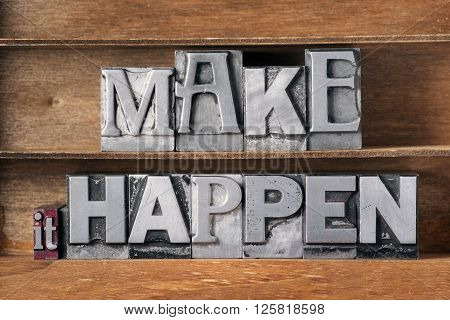make it happen phrase made from metallic letterpress type on wooden tray
