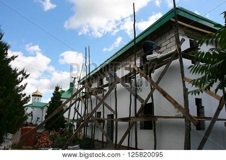 LUBESHIV UKRAINE - JULY 13 - Worker placing styrofoam sheet insulation to the wall in Lubeshiv on July 13 2013.