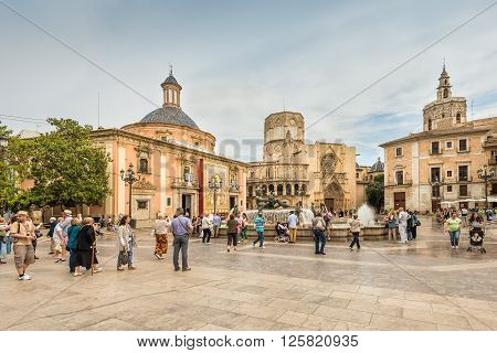 Valencia Spain - May 18 2014: Fountain at the Plaza de la Virgen with Basilica and cathedral in the background. People are scattered over the square in cloudy weather.