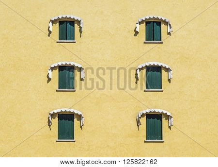 Six windows with green shutters closed on the yellow wall of the old Italian house in Pordenone, Italy
