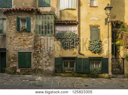 Facade of the old, yellow, typical Italian house with green closed shuttered windows