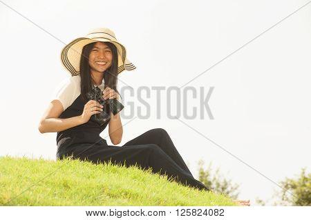 Pretty Asian young  woman sit on mound seeking binoculars.