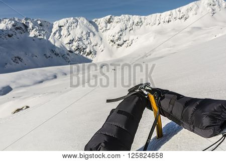 Down Mittens Clipped Carabiner On A Yellow Ice Axe And A Ridge In The Background.