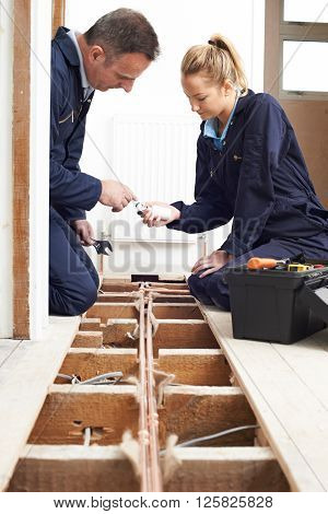Plumber And Apprentice Fitting Central Heating System