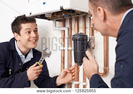 Trainee Plumber Working On Central Heating Boiler