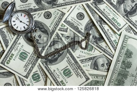 Background texture of banknotes in denominations of one hundred dollars scattered on a table and an old pocket watch