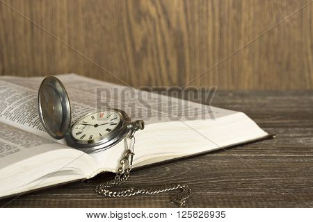Open book on which lie the old vintage pocket watch with chain. Focus is on the clock