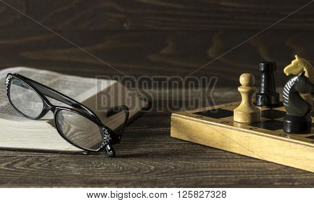 Open book with glasses lying near a chessboard with a pawn and a knight on a wooden background