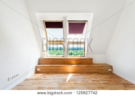 Empty Room of New Home with Wood Floors White Walls and Bright Skylights