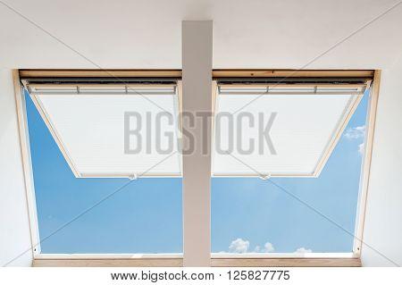 A modern open skylights (mansard windows) in an attic room against blue sky