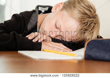 Sleeping Child With Head On Arms Next To Homework