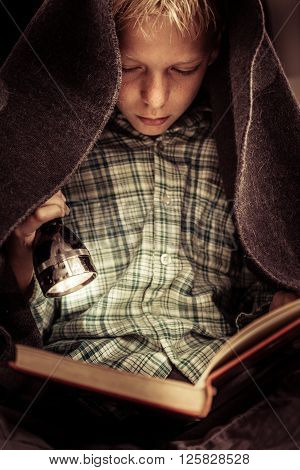 Child Reading Book Under Covers With Flashlight