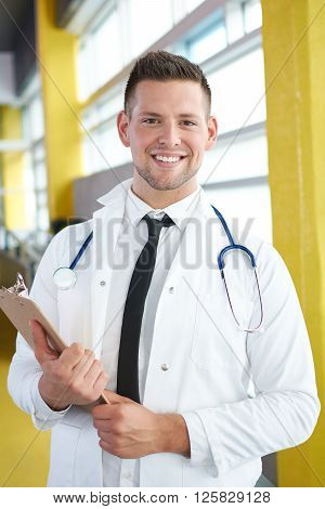 Friendly and handsome of a man practitioner standing in a glass hall office of the clinic and examining documents
