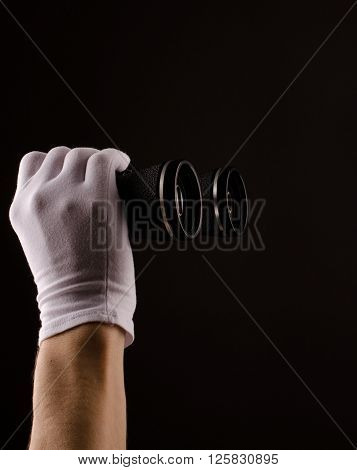 Male hands with white gloves holding binoculars
