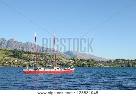 A red boat is sailing in blue Lake Wakatipu Queenstown New Zealand.