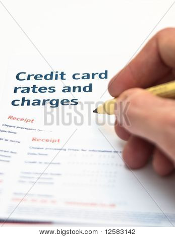 Hand Holding Pen Over Cedit Card Charges