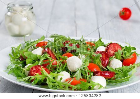Salad with tomatoes mozzarella arugula fried sausage on a white dish on a white rustic table balls of mozzarella cheese in a glass jar on the background studio light horizontal close-up macro