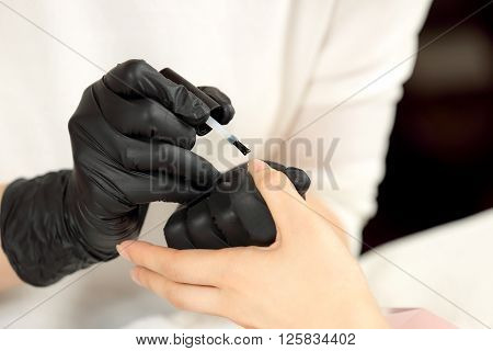 Manicurist cover colorless varnish nails client. Manicure master in black gloves does manicure
