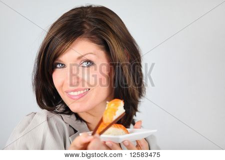 Portrait of a young woman eating a sushi with chopsticks on white background