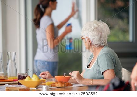 Senior woman having breakfast watching a young woman cleaning the windows