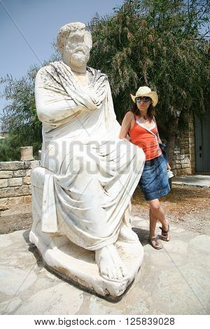 woman traveler tourist leaning on marble roman man statue from V century B.C. behind Ayios or Agios Titos Basilica at ancient city Gortyn greek monument in Crete Greece Europe