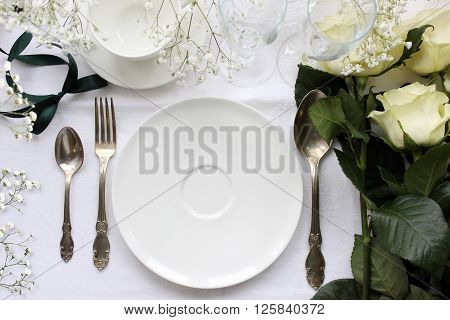 Wedding table Mockup with roses. Vintage fashion photography. Wedding dinner design. Place card reserved card. Beautiful dishware antique silver cutlery.