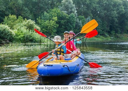 Active happy family. Girl with her brother and mother having fun together enjoying adventurous experience kayaking on the river on a sunny day during summer vacation