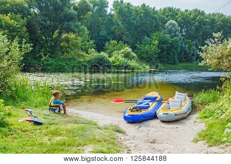 Active boy resting after adventurous experience kayaking on the river on a sunny day during summer vacation