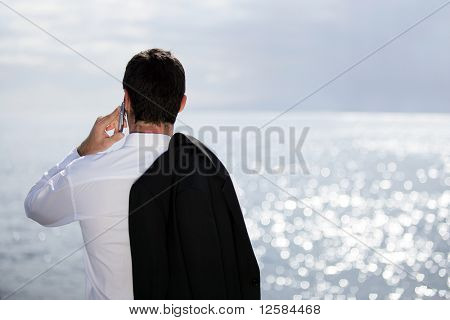 Joven en traje con una cara de teléfono al mar