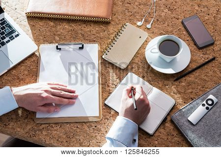 Businessman making notes in notebook laptop coffee and smartphone around. Cork table only hands seen. Concept of work.