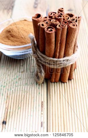 Cinnamon sticks and powder studio shot wood surface