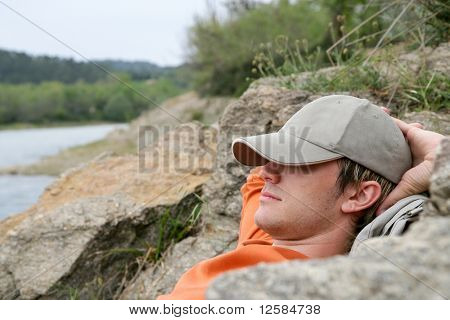 Young man relaxing at a lakeside