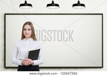 Businesswoman with folder in hands. White board at background three lamps above. Concept of education.