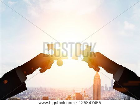 Teamwork concept with businessmen putting puzzle pieces together on cityscape background with sunlight