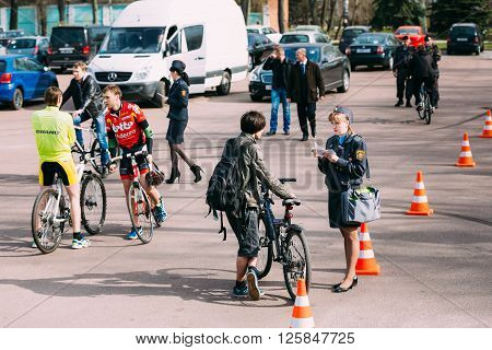 Gomel, Belarus - April 10, 2015: Female traffic road police officer inspector make registration a bicycle at the opening of cycling season in the city on Lenin Square