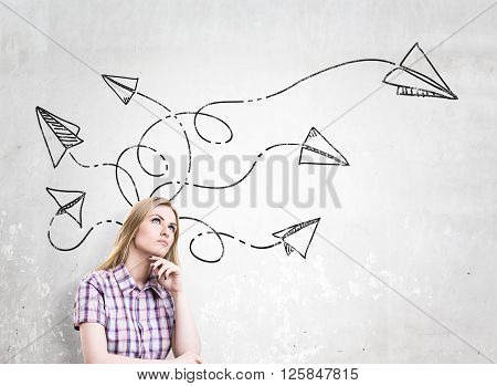 Woman in checked shirt with hand at chin paper planes drawn over her head dreaming. Concrete background. Concept of new idea.
