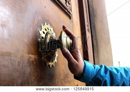 Old bronze door handle pushed by mans hand. Polished bronze door handle on the wooden door. Mans' hand touches the door handle.