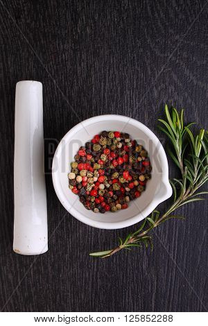 a mixture of peppers ( red black white ) in a white mortar with a sprig of rosemary