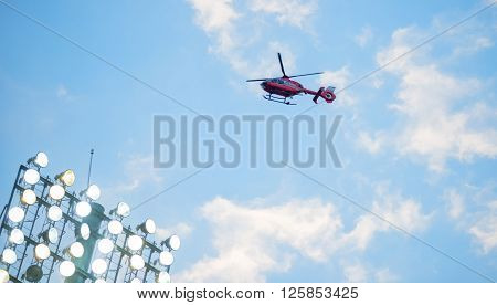 flying helicopter over fotball spotlights turned at sunset