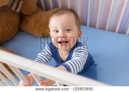 Baby boy sitting in the crib