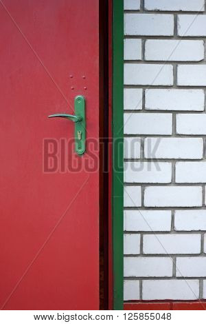 Iron red painted door in a brick house. The image of the entrance to the house. The door is poorly painted. The brick in some places peeled.