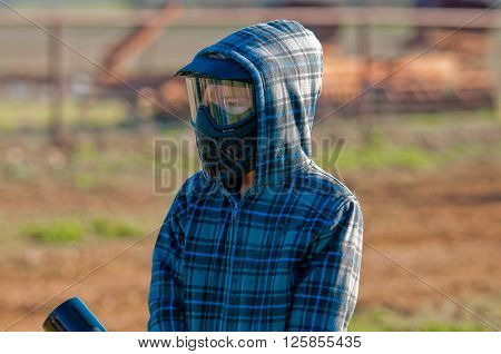 Boy in mask and hooded jacket playing paint ball outdoors.