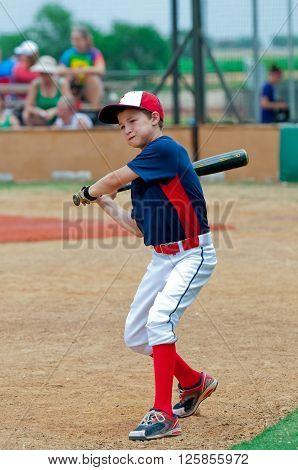 Youth little league baseball boy swinging the bat.