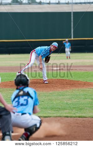 Teenage boy on the mound pitching during a game.