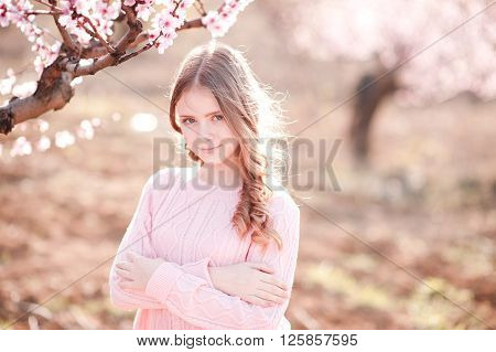Smiling teen girl 14-16 year old posing in peach garden outdoors. Looking at camera. Teenager hood.