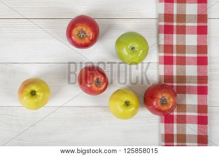 Colored whole apples placed on red checkered kitchen tablecloth. Top view.