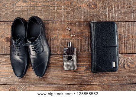 Top view photo of objects on wooden table. There are men's perfume, purse and shoes