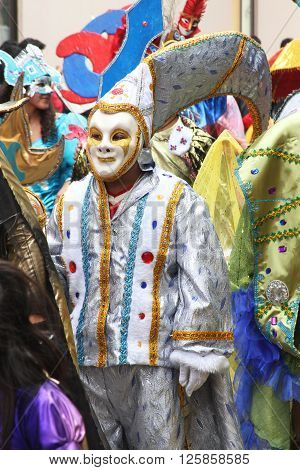 Cajamarca Peru - February 7 2016: Silver masked figure stands in midst of costumed people at Carnival parade Cajamarca Peru February 7 2016